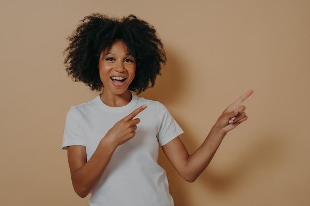 Giovane ragazza afroamericana che indossa abiti casual allegramente e ampiamente sorridente mentre indica con entrambe le mani e gli indici verso l'alto con un'espressione entusiasta sul viso, copia spazio