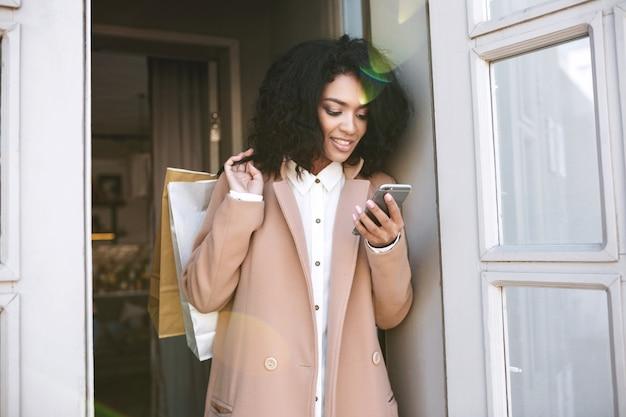 Giovane ragazza afroamericana con i capelli ricci scuri in piedi con i pacchetti e il telefono nelle sue mani ragazza piuttosto sorridente
