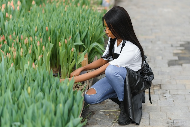 Giovane ragazza afroamericana, lavoratore con fiori in serra.