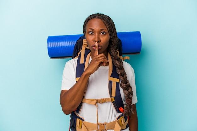 Giovane donna afroamericana escursionista isolata su sfondo blu mantenendo un segreto o chiedendo silenzio.