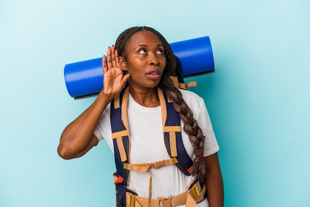 Giovane donna afroamericana della viandante isolata su fondo blu che prova ad ascoltare un gossip.