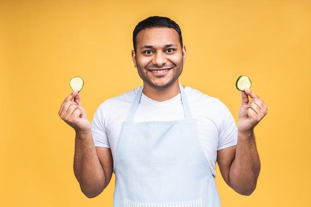 Giovane africano americano indiano fornello nero uomo che indossa il grembiule isolate su sfondo giallo. tenendo le fette di cetriolo.