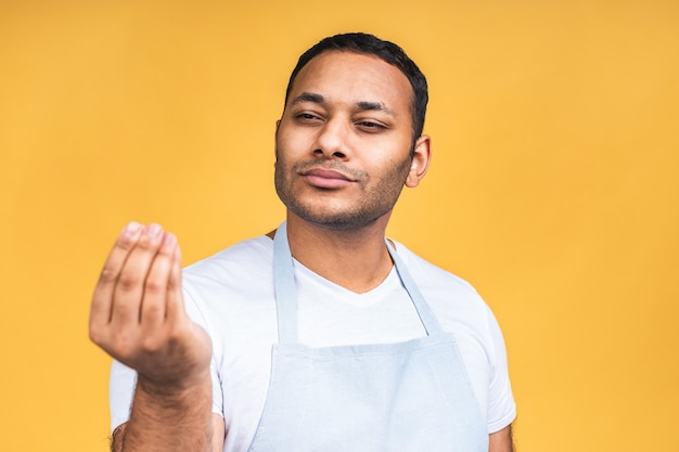 Giovane africano americano indiano fornello nero uomo che indossa il grembiule isolate su sfondo giallo.