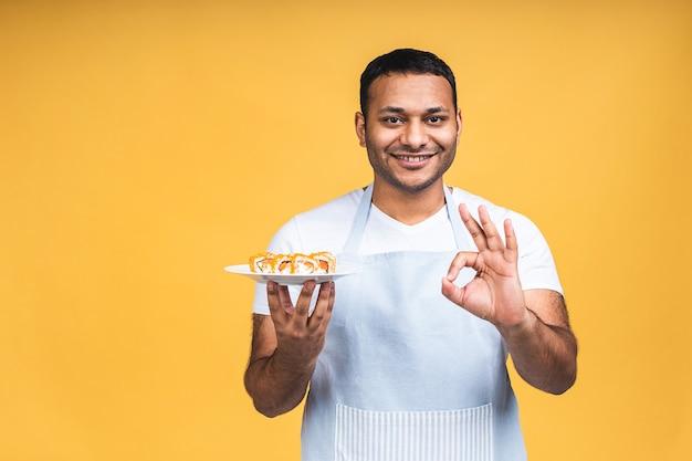 Giovane uomo nero indiano afroamericano che mangia sushi usando le bacchette sopra fondo giallo isolato. cuoco preparando il sushi.