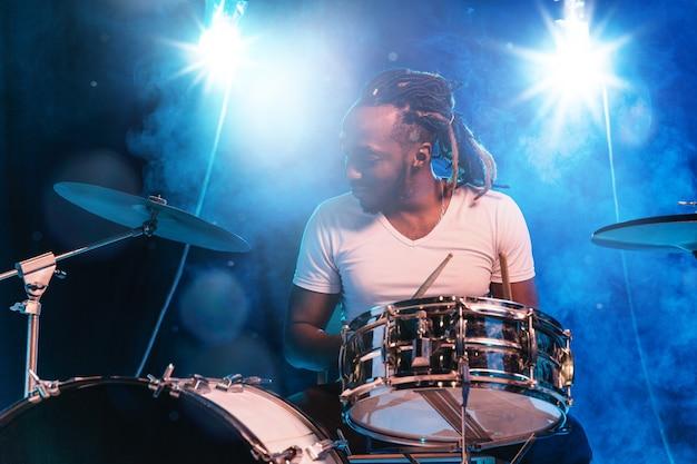 Giovane musicista jazz afro-americano o batterista che suona la batteria sulla parete blu nel fumo incandescente intorno a lui.