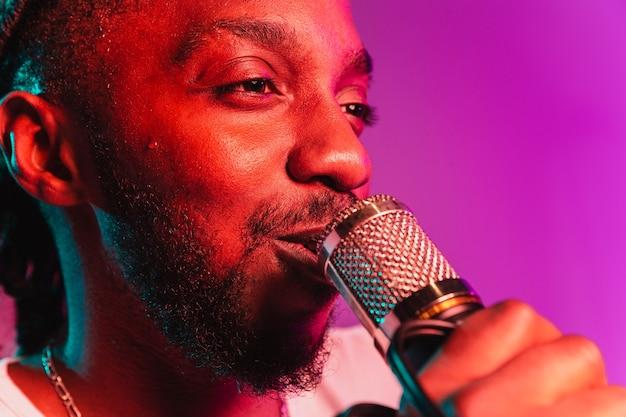 Giovane musicista jazz afroamericano che canta una canzone rosa sfumato