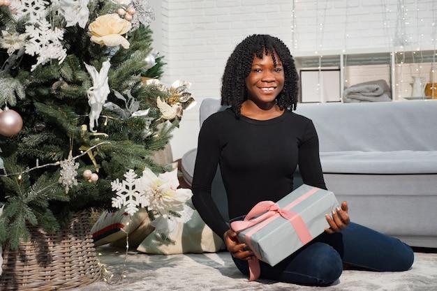 La giovane signora afroamericana si siede vicino a un albero di natale e tiene un regalo