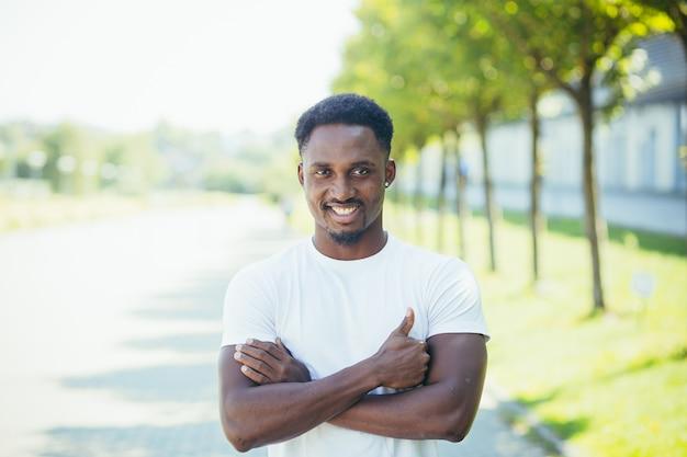 Il giovane atleta maschio afroamericano, durante una corsa mattutina, guarda la telecamera con le braccia incrociate, motivato e sorridente