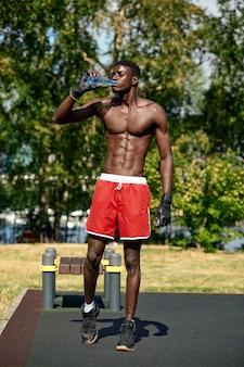 Il giovane afroamericano beve acqua mentre si allena nel parco sul campo sportivo, concetto di allenamento all'aperto, crossfit