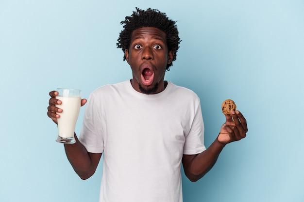 Giovane uomo afroamericano che mangia biscotti con gocce di cioccolato e beve latte su blue