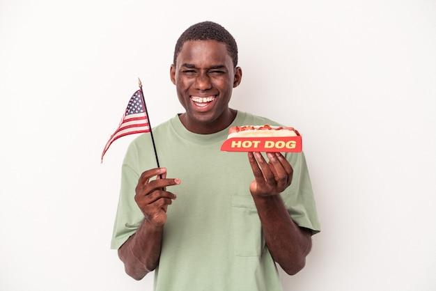 Giovane uomo afroamericano che mangia hot dog e tiene in mano la bandiera americana isolata su sfondo bianco