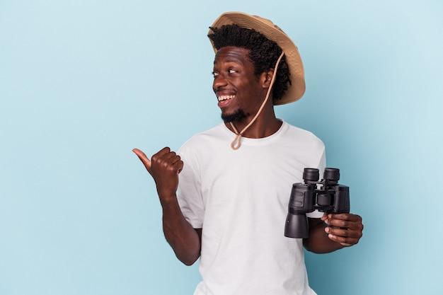 Il giovane uomo afroamericano che tiene il binocolo isolato su sfondo blu indica con il pollice lontano, ridendo e spensierato.
