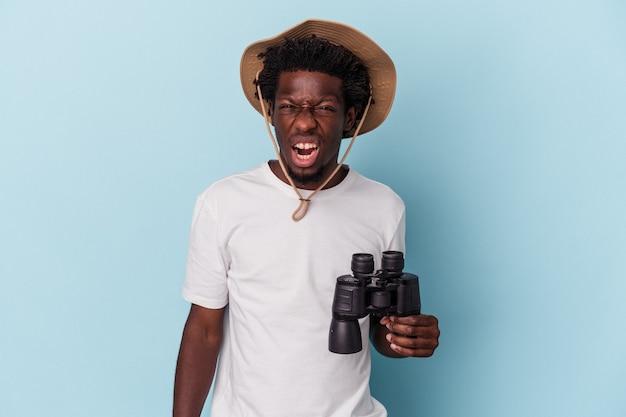 Giovane uomo afroamericano che tiene il binocolo isolato su sfondo blu urlando molto arrabbiato e aggressivo.