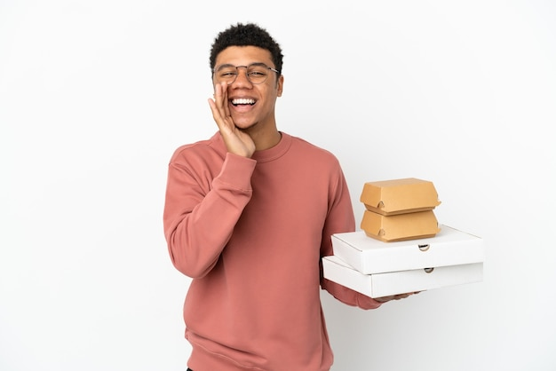 Giovane uomo afroamericano che tiene un hamburger e pizze isolate su fondo bianco che grida con la bocca spalancata