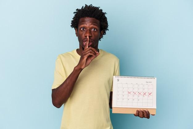 Giovane uomo afroamericano che tiene il calendario isolato su sfondo blu mantenendo un segreto o chiedendo silenzio.
