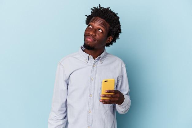 Giovane uomo afroamericano che tiene il telefono cellulare isolato su sfondo blu che sogna di raggiungere obiettivi e scopi