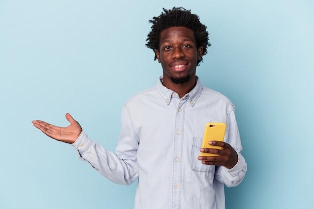 Giovane uomo afroamericano che tiene telefono cellulare isolato su fondo blu che mostra uno spazio della copia su una palma e che tiene un'altra mano sulla vita.