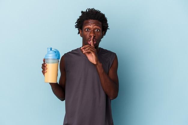 Giovane uomo afroamericano che tiene frappè proteico isolato su sfondo blu mantenendo un segreto o chiedendo silenzio.