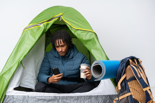 Giovane uomo afroamericano dentro una tenda verde di campeggio che tiene caffè da portare via e un cellulare