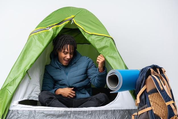 Giovane uomo afroamericano dentro una tenda verde di campeggio che fa gesto della chitarra