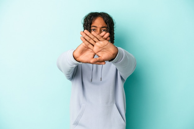 Giovane uomo afroamericano isolato su sfondo blu facendo un gesto di rifiuto