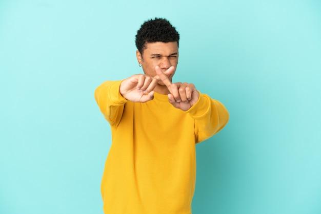 Giovane uomo afroamericano isolato su sfondo blu che fa un gesto di arresto con la mano per fermare un atto