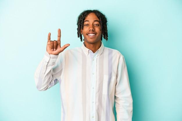Giovane uomo afroamericano isolato su sfondo blu che mostra un gesto di corna come un concetto di rivoluzione.