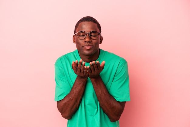 Giovane uomo afroamericano isolato su sfondo rosa piegando le labbra e tenendo i palmi delle mani per inviare un bacio d'aria.