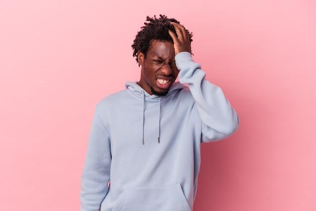 Giovane uomo afroamericano isolato su sfondo rosa dimenticando qualcosa, schiaffeggiando la fronte con il palmo e chiudendo gli occhi.