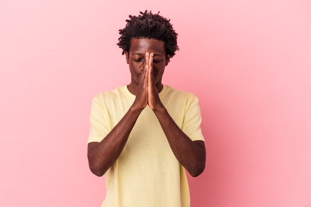 Il giovane uomo afroamericano isolato su sfondo rosa tenendosi per mano in preghiera vicino alla bocca, si sente sicuro.