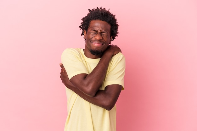 Il giovane uomo afroamericano isolato sugli abbracci rosa del fondo, sorridendo spensierato e felice.
