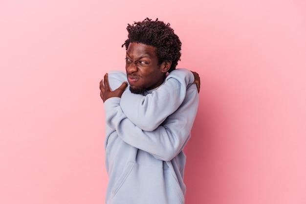 Il giovane uomo afroamericano isolato sugli abbracci rosa del fondo, sorride spensierato e felice.