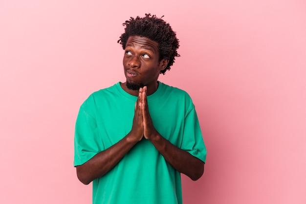 Giovane uomo afroamericano isolato su sfondo rosa pregando, mostrando devozione, persona religiosa in cerca di ispirazione divina.
