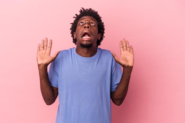 Giovane uomo afroamericano isolato su sfondo rosa che urla al cielo, alzando lo sguardo, frustrato.