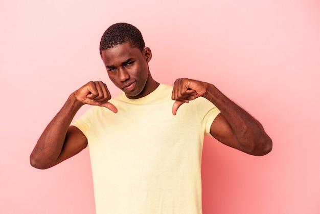 Giovane uomo afroamericano isolato su sfondo rosa che mostra il pollice verso il basso, concetto di delusione.
