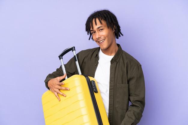 Giovane uomo afroamericano isolato sulla parete porpora in vacanza che tiene una valigia di viaggio come una chitarra