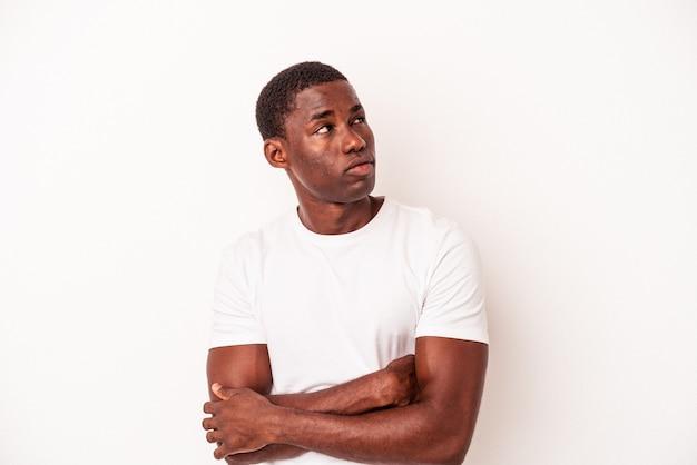 Giovane uomo afroamericano isolato su sfondo bianco che sogna di raggiungere obiettivi e scopi