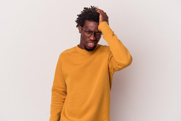 Giovane uomo afroamericano isolato su sfondo bianco dimenticando qualcosa, schiaffeggiando la fronte con il palmo e chiudendo gli occhi.