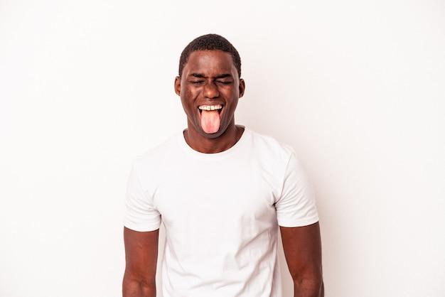 Giovane uomo afroamericano isolato su sfondo bianco divertente e amichevole conficca fuori la lingua.