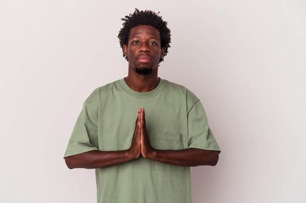 Giovane uomo afroamericano isolato su sfondo bianco pregando, mostrando devozione, persona religiosa in cerca di ispirazione divina.