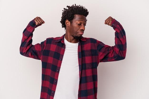 Giovane uomo afroamericano isolato su sfondo bianco che mostra gesto di forza con le braccia, simbolo del potere femminile