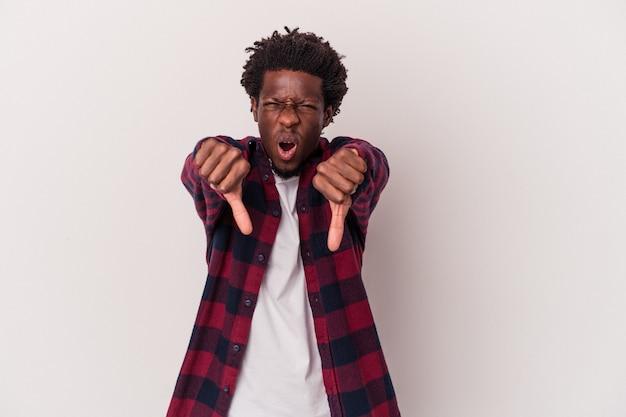 Giovane uomo afroamericano isolato su sfondo bianco che mostra il pollice verso il basso ed esprime antipatia.