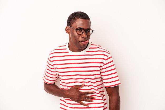 Il giovane uomo afroamericano isolato su fondo bianco tocca la pancia, sorride dolcemente, mangia e concetto di soddisfazione.