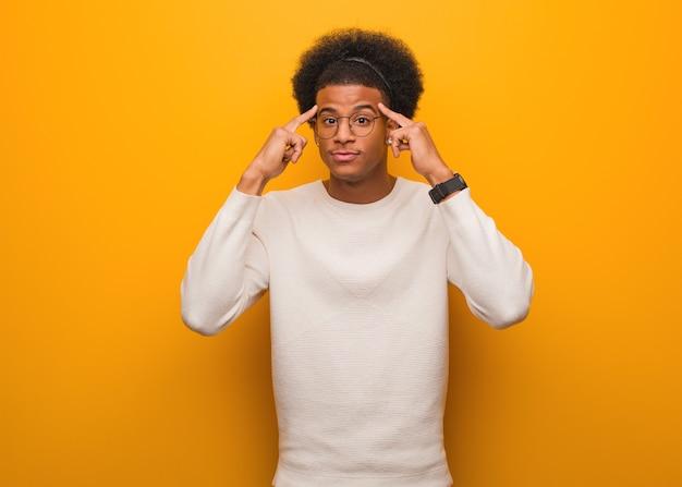 Giovane uomo afroamericano sopra una parete arancione che fa un gesto di concentrazione