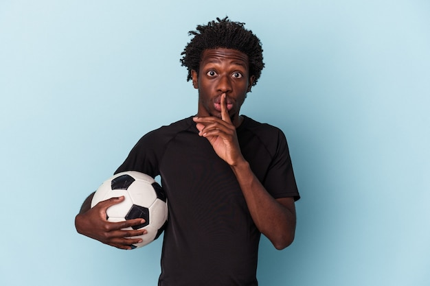 Giovane uomo afroamericano che gioca a calcio isolato su sfondo blu mantenendo un segreto o chiedendo silenzio.