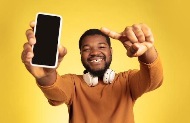 Ritratto di giovane uomo afro-americano isolato su sfondo giallo studio, espressione facciale.