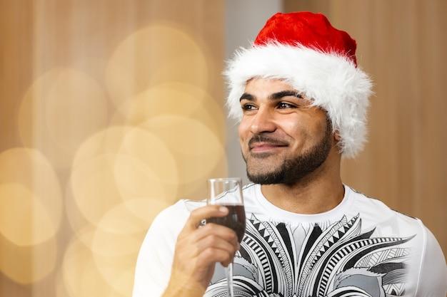 Giovane uomo afroamericano in berretto santa che beve vino rosso