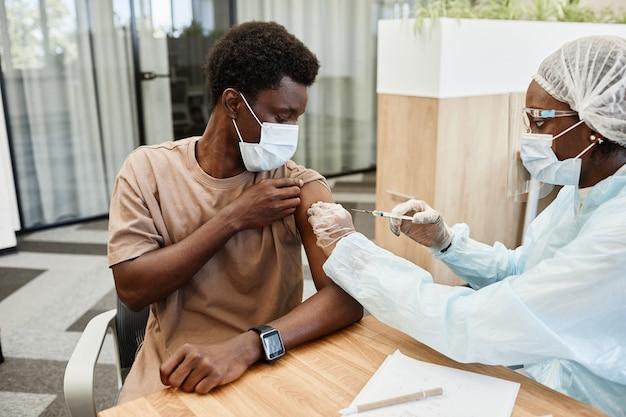 Giovane uomo afroamericano seduto nell'ufficio del medico e si fa vaccinare contro l'influenza nel braccio