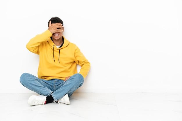 Giovane uomo afroamericano seduto sul pavimento isolato su sfondo bianco che copre gli occhi con le mani e sorride