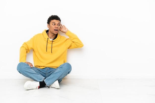 Giovane uomo afroamericano seduto sul pavimento isolato su sfondo bianco ascoltando qualcosa mettendo la mano sull'orecchio